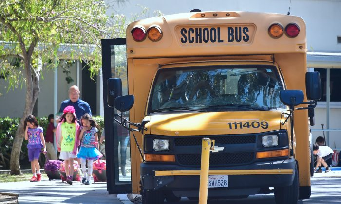 Children walk past a School Bus in Monterey Park, California on April 28, 2017. (Frederic J. Brown/AFP/Getty Images)