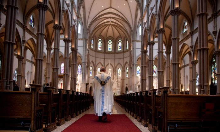 A priest walks to the sanctuary following a mass Photo by Jeff Swensen/Getty Images