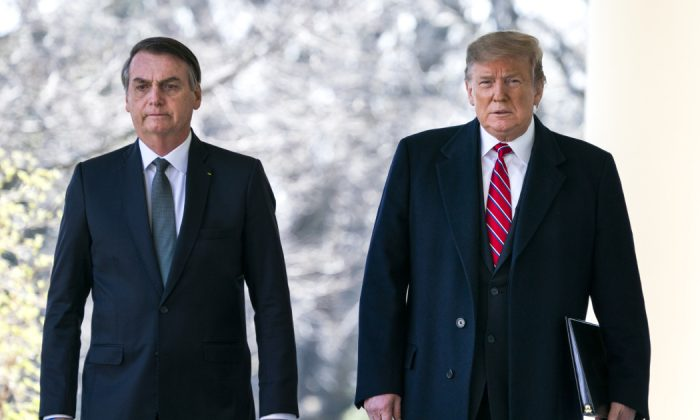 Photo: U.S. President Donald Trump (R) and Brazilian President Jair Bolsonaro (L) walk down the Colonnade before a press conference at the Rose Garden of the White House in Washington, DC on March 19, 2019.