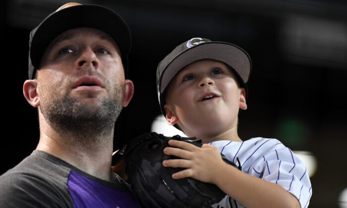 A father and son watch batting practice prior to a game between the Colorado Rockies and Arizona Diamondbacks at Chase Field on August 20, 2019 in Phoenix, Arizona. (Photo by Norm Hall/Getty Images)