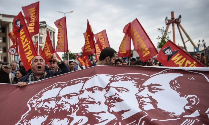 TOPSHOT - People hold a banner picturing Communist figures including (From L) German philosopher and communist theoretician Karl Marx, German philosopher and communist thinker Friedrich Engels, Soviet leader Vladimir Ilitch Lenin, Soviet leader Josph Stalin and Chinese late communist leader Mao Zedong, as they gather in Bakirkoy district as part of the the May Day rally, in Istanbul, on May 1, 2017. / AFP PHOTO / OZAN KOSE        (Photo credit should read OZAN KOSE/AFP via Getty Images)