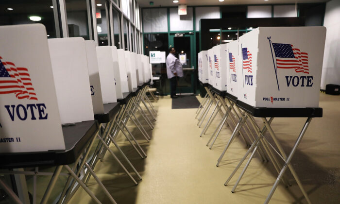 Photo credit: Voting booths are setup at the Yuengling Center on the campus of University of South Florida as workers prepare to open the doors to early voters in Tampa, Fla, on Oct. 22, 2018. (Joe Raedle/Getty Images)
